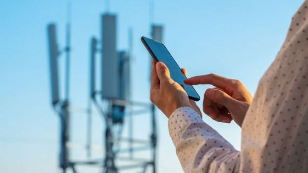 5G communications tower with man using mobile phone